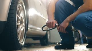 Auto mechanic pumps wheel of a car