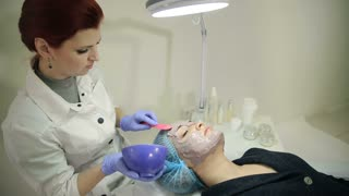 Beautician applying cosmetic mask on the face