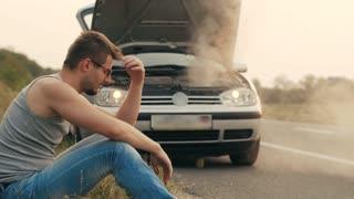Car with overheated engine and sad man