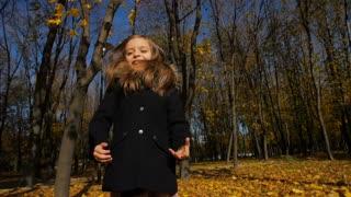 Cheerful little girl runs at park