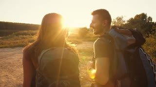 Couple hiking with backpacks at sunset