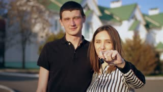 Couple in front of new house with the keys