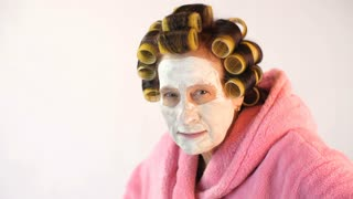 Evil wife with a cosmetic mask and curlers