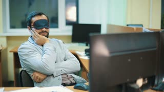 Executive with blindfold sleeping at work