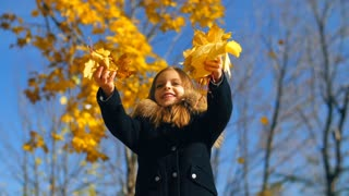 Little girl throws leaves up