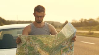 Man Reading Map on the Car's Hood
