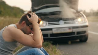 Man sitting in a front of broken car