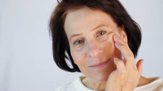 Middle-aged woman applying cream