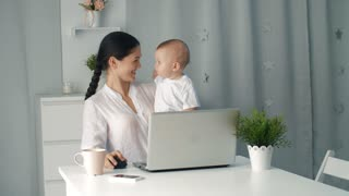 Mother woman with a toddler working at the computer