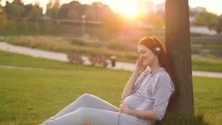 Pregnant Woman listening to music on sunset