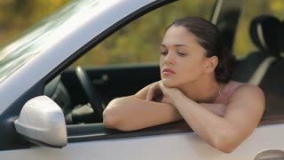 Sad young woman in a car
