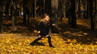 Smiling little girl runs at autumn park