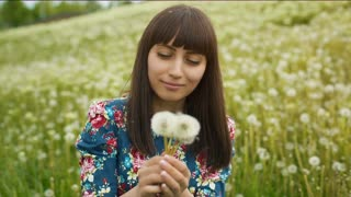 Smiling Woman Blow on a Dandelion