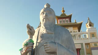 Statue of a wise man in a front of buddhist temple