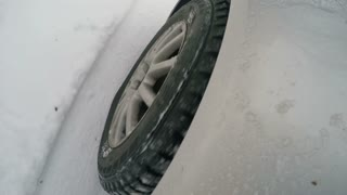 The wheel of the car on the snowy road