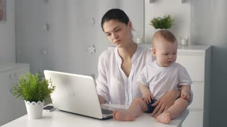Tired mother with baby working on laptop