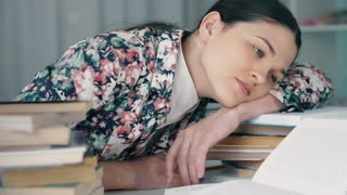 Tired woman lies on books