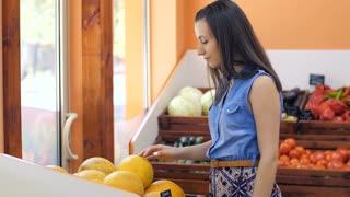 Woman Choosing Melon at Market