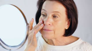 Woman moisturizes the face with cream