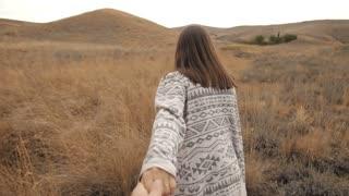 Woman runs holding a man's hand