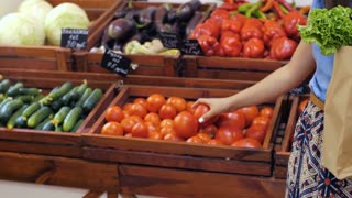 Woman with bag of vegetables at store