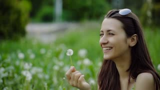 Woman Blowing Dandelion on a Summer Field