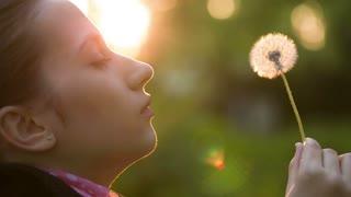 Woman Blowing on a Dandelion