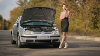 Woman calling by the phone near broken car