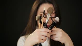 Woman hiding behind makeup brushes