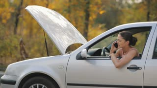 Woman in a broken car talking by the phone