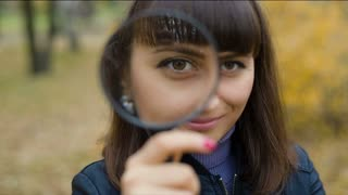 Woman looking through a magnifier