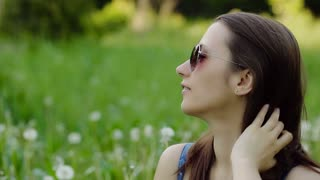 Woman Preens and blow on dandelions