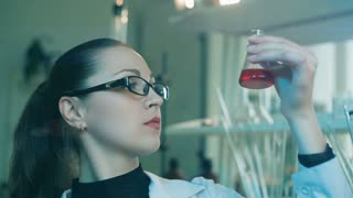 Woman researching flask in a laboratory