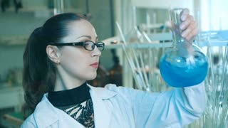 Woman shakes flask in a laboratory