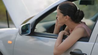 Woman sitting in broken car calling for help