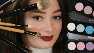Woman with makeup brushes and eyeshadow