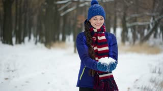 Young cheerful woman throwing up snow