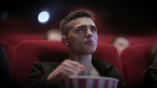 Young Stylish Man watching movie in cinema