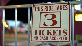 3 tickets to ride sign at carnival with ride spinning in background 4k