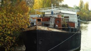 Abandoned house boat docked on river 4k