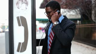 African American male having conversation on pay phone