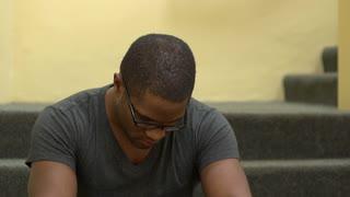 African American male rubbing head upset