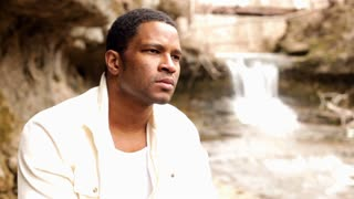 African American male sitting in front of waterfall