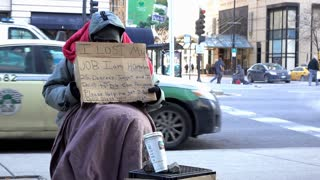 African American male sitting on sidewalk with sign asking for help 4k