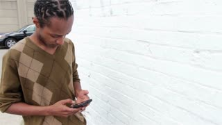 African American male texting and walking