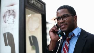 African American Man talking on Payphone
