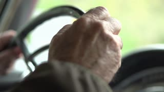 Aged hands Driving classic car