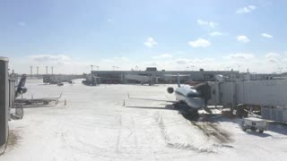 Airplane at terminal gate of snow covered airport