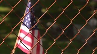 American flag behind chain link fence waving 4k