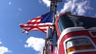 American Flag blowing above firetruck on ladder 4k